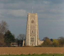 The grey flint square tower of Lavenham Church, with fields in the foreground and a cloudy sky in the background