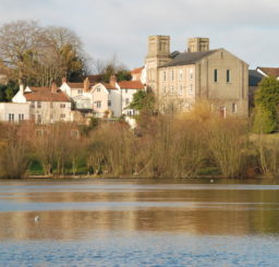 view of buildings across Diss Mere in the autumn