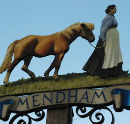 Mendham village sign of a woman leading a horse