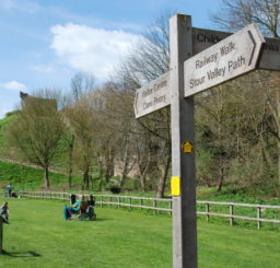 Stour Valley Path wooden finger post sign at Clare Castle Country Park on a sunny day