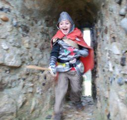 child having fun dressed as a knight exploring a flint tunnel at Framlingham Castle