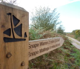 Woooden finger post showing the Sailors' Path logo, Snape Warren 2 miles and Snape Maltings 4 miles