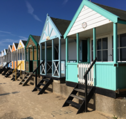Colourful beach huts along the prom at Southwold on a sunny day