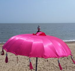 a large bright pink parasol on the sandy beach at Felixstowe