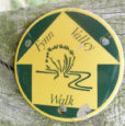 green and yellow Fynn Valley Path waymarker disc attached to a wooden fence