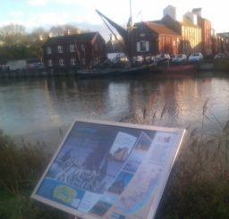 a view of Snape Maltings and a barge from the Sailors' Path, with an information board in the foreground