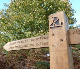 a wooden Sailors' Path finger post with the black barge logo and pointing to Snape Warren 1.6 miles and Snape Maltings 3.5 miles, on a sunny day