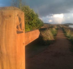 a wooden waymarker post along the Sailors' Path, bathed in orange sunlight with storm clouds in the distance
