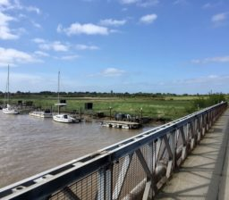 view towards Walberswick across the Bailey Bridge at Southwold, with moored boats, then green meadows visible, on a sunny day