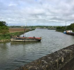 A view down the River Deben from Wilford Bridge, with two boats moored alongside the grassy banks