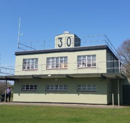 the Martlesham Control Tower Museum - a two-story pale green square building with a large 30 painted in black on a square structure on the roof, on a sunny day