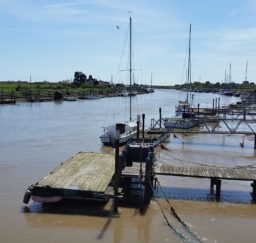 a view of boats moored at jetties along the River Blyth at Southwold Harbour on a sunny day