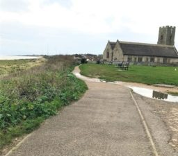 a tarmac footpath with greenery and the sea on the left and leading to All Saints' and St Margaret's Church, Pakefield, on the right