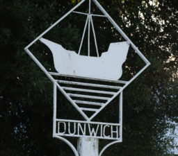 the white Dunwich village sign depicting an large old sailing ship enclosed within a square and with lines underneath to depict the sea
