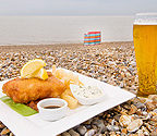 a delicious looking portion of fish, chips and mushy peas with a pint of beer on Aldeburgh Beach, with a blue and red striped windbreak and the sea in the background