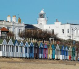 the large white painted Southwold lighthouse, with multi-coloured beach huts and the sandy beach in the foreground