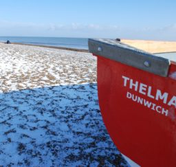 Dunwich Beach in winter - snow covers the shingle with fishermen's tents spread out along the beach. The stern of a bright red rowing bat called