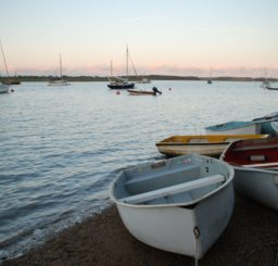 a view across the water at Bawdsey - lots of sailing dinghies moored in the water and several small rowing boats tied up on the beach
