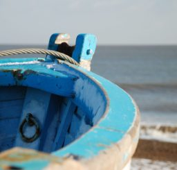 in focus taking up most of the picture is the prow of a tatty blue painted rowing boat, with the shingle beach and sea at Dunwich visible in the background